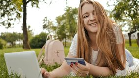 Pretty young student girl makes purchases online using a credit card and laptop computer. Stock Images