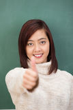 Pretty young student giving a thumbs up gesture Stock Photography