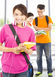 Pretty young student holding books and earphone with classmates Stock Photos