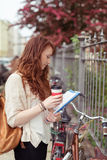 Pretty young student standing reading her notes Stock Image