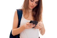 Pretty young students girl with blue backpack on shoulder and mobile phone in hands posing isolated on white background. Pretty young students girl with blue Royalty Free Stock Photos