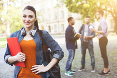 Pretty young students are talking on break. Enjoying university life. Portrait of attractive girl standing and holding a book. She is lookinh forward and smiling Royalty Free Stock Photos