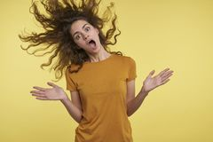 Pretty young surprised woman with curly flying hair, she happy of something, cant belive, isolated over yellow royalty free stock photography