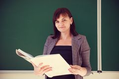 Pretty young teacher is standing with book near blackboard Stock Images