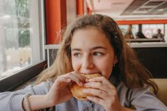 Pretty young teen girl with an appetite eating a hamburger in a cafe. Pretty young teen girl with an appetite eating hamburger in a cafe royalty free stock photography