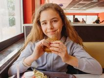 Pretty young teen girl with an appetite eating a hamburger in a cafe. Pretty young teen girl with an appetite eating hamburger in a cafe royalty free stock photos