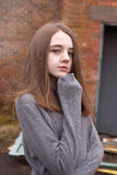 Pretty young teenage girl huddling in her jumper with a derelict Stock Photos