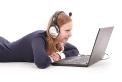 Pretty young teenage girl with laptop and headphones lying on the floor Stock Photography