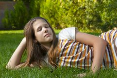 Pretty young teenage girl resting on the grass Royalty Free Stock Image