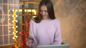 Pretty young teenage girl shopping online using her credit card and laptop computer. 4 k. Woman doing online shopping at stock video footage