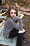 Pretty young teenage girl sitting on some old doors outdoors Royalty Free Stock Images