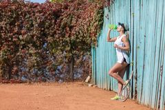 Pretty young female tennis player drinking water eyes closed. Royalty Free Stock Image