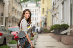 Pretty young tourist woman in casual clothes on a sidewalk of the street. Curly female on vacation in european city Stock Images