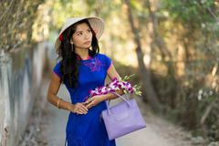 Pretty young Vietnamese woman carrying flowers Stock Photography