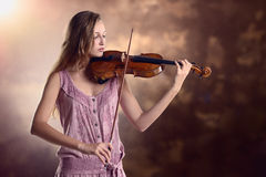 Pretty young violinist playing the violin Stock Images