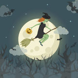 Pretty young witch on a broomstick flying over the spooky forest Stock Photo