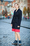 Pretty young woman. Standing on an old city square in twilight Stock Photos