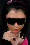 Pretty young woman. Young women wearing black sunglasess, isolated on black background Stock Photography