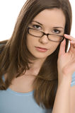 Pretty young woman. Looks at camera over top of glasses stock photo