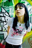 Pretty Young Woman. A pretty young woman with jet black hair and big hoop earrings standing in front of a wall with graffiti.  Image reveals her left arm tattoo Stock Image