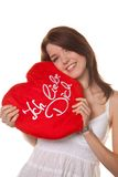Pretty young woman. Young girl gives away a love gift, heart-shaped pillow Royalty Free Stock Images