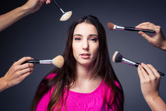 Pretty, young woman in the able care of  make-up artist Royalty Free Stock Photos