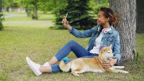Pretty young woman African American student is making video call using smartphone and petting her dog sitting on lawn in. Pretty young woman African American stock video