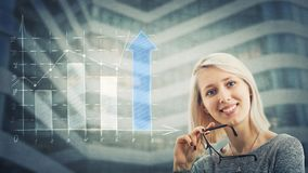 Smile. Pretty young woman analyst holding glasses in her hand and a rising graph with arrow going up. Business industries profit, growth and progress symbol royalty free stock photo