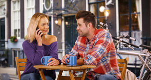 Pretty young woman answers phone call in the middle of her date Royalty Free Stock Image