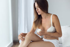 Pretty young woman applying body cream on legs. Royalty Free Stock Photos