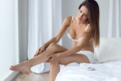 Pretty young woman applying body cream on legs. Stock Photography