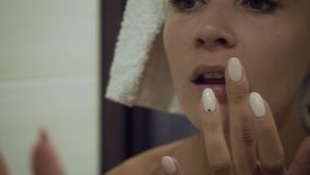 Pretty young woman applying lipbalm in the bathroom. stock video footage