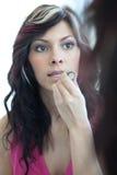 Pretty young woman applying lipstick. Pretty young woman applying mascara Royalty Free Stock Photos