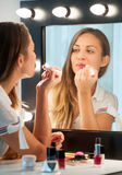 Pretty young woman applying lipstick. Pretty young woman with long brown hair sitting at a dressing table applying lipstick, view to her reflection in the mirror Royalty Free Stock Photos