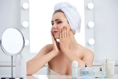 Aplying creams and lotions. Pretty young woman applying lotions on face at her vanity Royalty Free Stock Photo