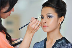 Pretty young woman applying makeup by makeup artist Stock Image