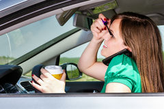 Pretty Young Woman Applying Makeup, Speaking On Phone And Drinking Coffee While Driving Royalty Free Stock Image