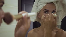 Young woman applying powder with big brush in the bathroom. stock video