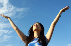 Pretty young woman with arms raised. Against blue sky Royalty Free Stock Images