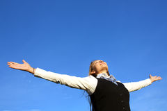 Pretty young woman with arms raised. Against blue sky Stock Images