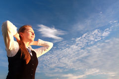 Pretty young woman with arms raised. Against blue sky Royalty Free Stock Image
