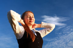 Pretty young woman with arms raised. Against blue sky Stock Photo
