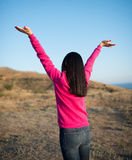 Pretty young woman with arms raised Stock Images