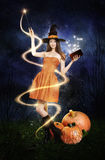 Pretty young woman as halloween witch. With magic wand, magic book and pumpkin's Stock Images