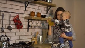 Pretty young woman with a baby in her arms in modern kitchen showing to child jar of pasta. Happy family concept. Woman stock video