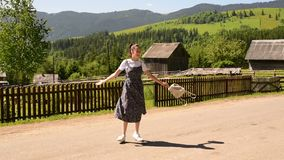 Pretty young woman with a backpack happily spinning. Sunny summer day. Village and green mountains in the distance.  stock footage