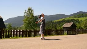 Pretty young woman with a backpack happily spinning. Sunny summer day. Village and green mountains in the distance.  stock video