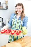 Pretty young woman baking tasty muffins at home royalty free stock photos