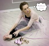 A pretty young woman ballerina dreams sitting on the floor in a royalty free stock image