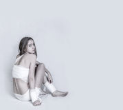 Pretty young woman with a bandage dressings on her body. Over grey background royalty free stock photos